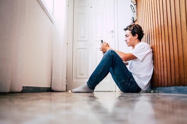 Jonge blanke tiener die de smartphone op de vloer gebruikt