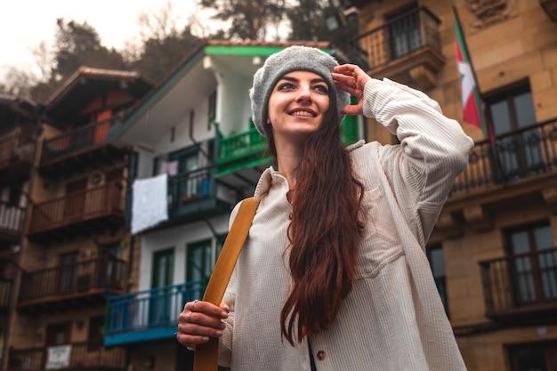 Jonge blanke toeristenvrouw die een oude stad met kleurrijke huizen bezoekt