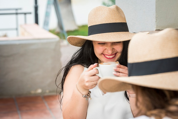Jonge blanke trendy meid lacht veel met vrienden in de café-bar en drinkt een cappuccino-drankje