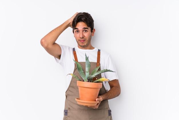 Jonge blanke tuinman man met een plant geïsoleerd wordt geschokt, ze heeft belangrijke vergadering onthouden.
