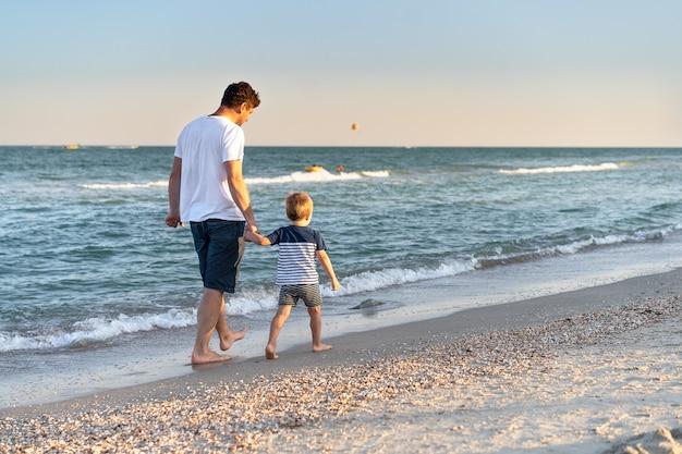 Jonge blanke vader met zoontje lopen warme zomerdag langs de kust. zomer familievakantie concept. vriendschap vader en zoon. gelukkige jeugd op het strand met de ouder. vrije ruimte voor tekst