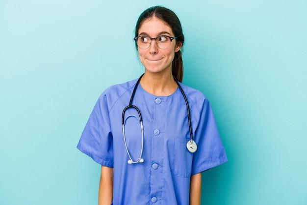 Jonge blanke verpleegster geïsoleerd op blauwe achtergrond verward, voelt zich twijfelachtig en onzeker.