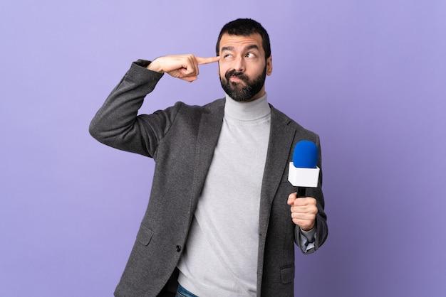 Jonge blanke verslaggever man over geïsoleerde paarse muur