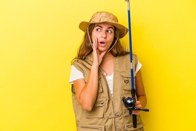 Jonge blanke vissersvrouw die een hengel vasthoudt die op een gele achtergrond is geïsoleerd, zegt een geheim heet remnieuws en kijkt opzij