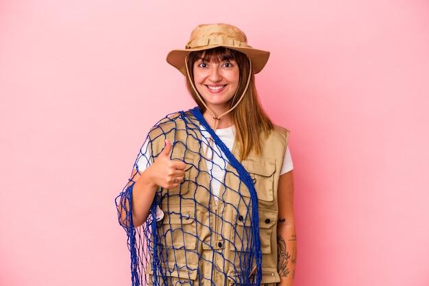 Jonge blanke vissersvrouw met net geïsoleerd op blauwe achtergrond glimlachend en duim omhoog