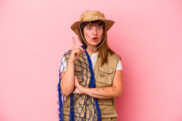 Jonge blanke vissersvrouw met net geïsoleerd op blauwe achtergrond met een geweldig idee, concept van creativiteit.