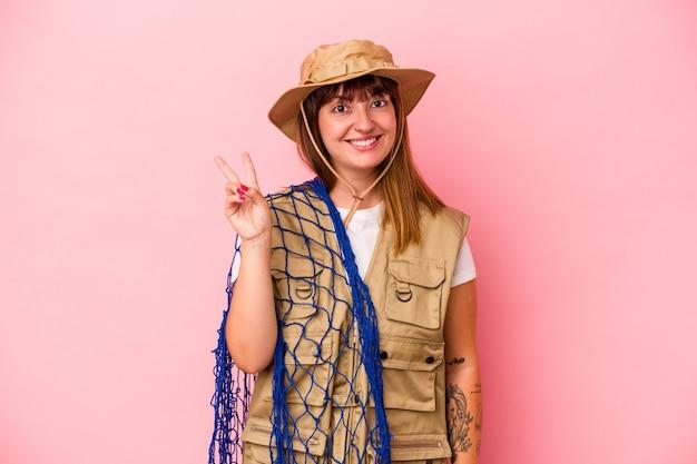 Jonge blanke vissersvrouw met net geïsoleerd op blauwe achtergrond vrolijk en zorgeloos met een vredessymbool met vingers.