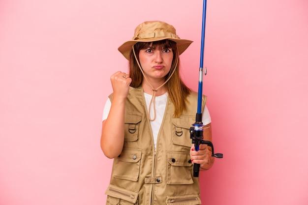 Jonge blanke vissersvrouw met staaf geïsoleerd op blauwe achtergrond met vuist naar camera, agressieve gezichtsuitdrukking.