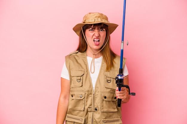 Jonge blanke vissersvrouw met staaf geïsoleerd op blauwe achtergrond schreeuwend erg boos en agressief.