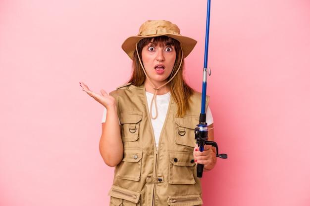 Jonge blanke vissersvrouw met staaf geïsoleerd op blauwe achtergrond verrast en geschokt.