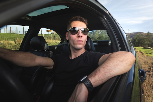 Jonge blanke volwassene in een sportwagen
