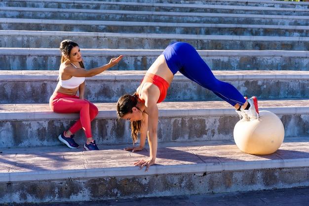 Jonge blanke vriendinnen doen oefeningen en strekken zich buiten uit - concept van gezonde levensstijl