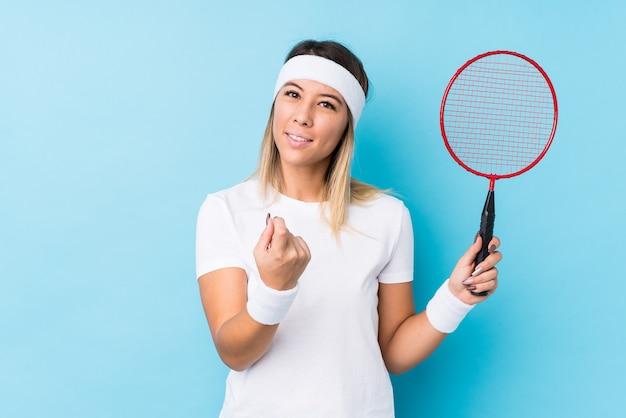 Jonge blanke vrouw badminton spelen geïsoleerd met vinger naar je wijzend alsof uitnodigend dichterbij komen.