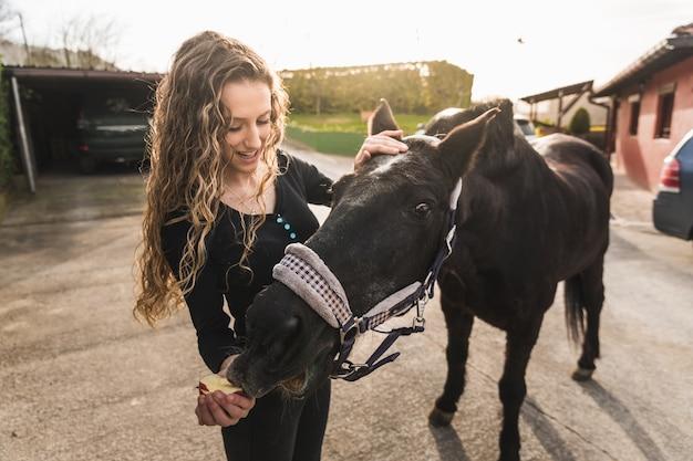 Jonge blanke vrouw bereidt een wit paard voor op een ritje