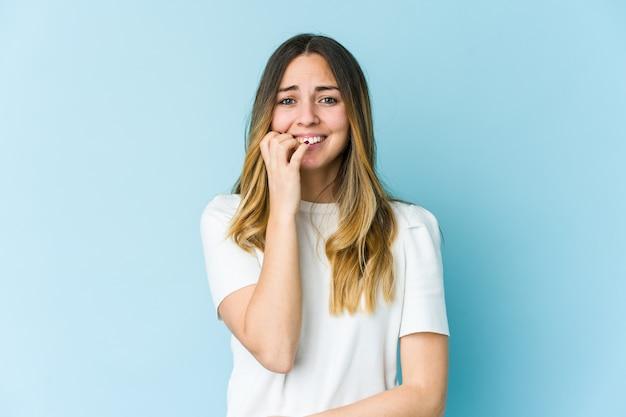 Jonge blanke vrouw bijt nagels, nerveus en erg angstig.