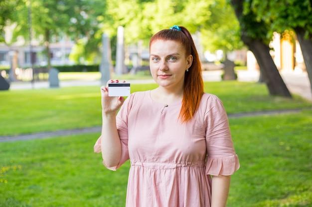 Jonge blanke vrouw blijft in park en toont witte creditcard met zwarte magneetlijn.