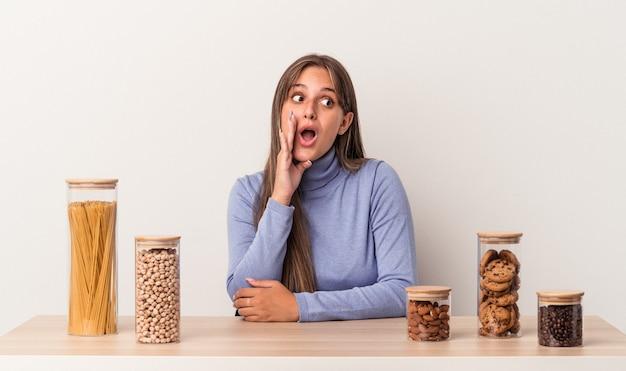 Jonge blanke vrouw die aan een tafel zit met een voedselpot geïsoleerd op een witte achtergrond, zegt een geheim heet remnieuws en kijkt opzij