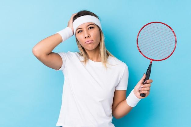 Jonge blanke vrouw die badminton speelt wordt geschokt, ze herinnert zich een belangrijke ontmoeting.
