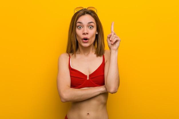Jonge blanke vrouw die bikini en zonnebril draagt met een geweldig idee, concept van creativiteit.