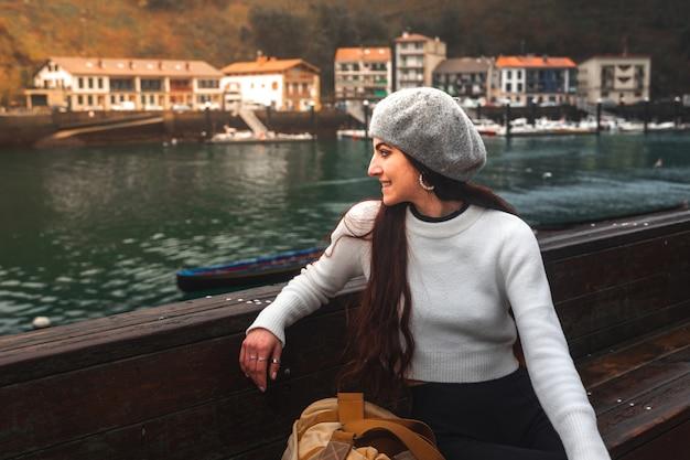 Jonge blanke vrouw die de baai van pasaia in baskenland bekijkt.