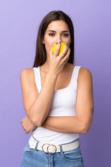Jonge blanke vrouw die een appel eet
