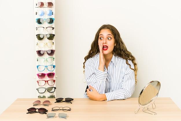 Jonge blanke vrouw die een bril geïsoleerd probeert, zegt een geheim heet remnieuws en kijkt opzij