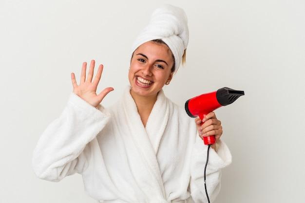 Jonge blanke vrouw die een föhn houdt die op wit wordt geïsoleerd glimlachend vrolijk tonend nummer vijf met vingers.