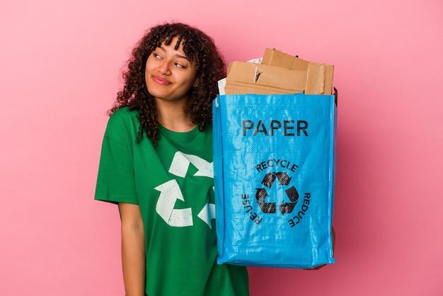 Jonge blanke vrouw die een gerecycled plastic geïsoleerd op een roze muur houdt en droomt van het bereiken van doelen en doeleinden