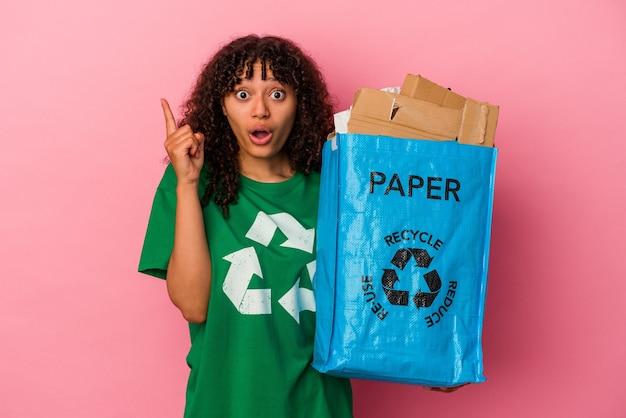 Jonge blanke vrouw die een gerecycled plastic houdt dat op roze muur wordt geïsoleerd die een idee, inspiratieconcept heeft.