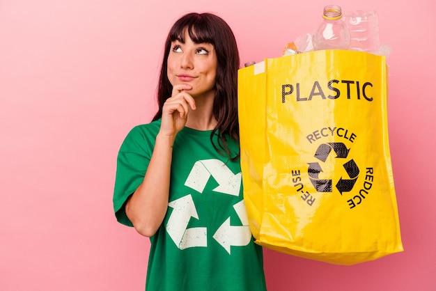 Jonge blanke vrouw die een gerecycleerde plastic zak houdt die op roze achtergrond wordt geïsoleerd en zijwaarts kijkt met twijfelachtige en sceptische uitdrukking.