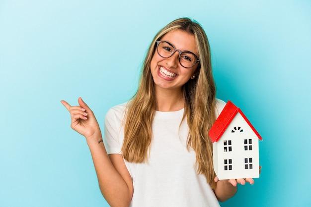Jonge blanke vrouw die een huismodel houdt dat op blauwe achtergrond wordt geïsoleerd die en opzij glimlacht richt, iets op lege ruimte toont.