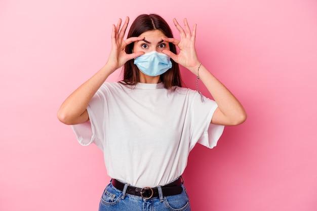 Jonge blanke vrouw die een masker voor virus draagt dat op roze muur wordt geïsoleerd en ogen open houdt om een succeskans te vinden