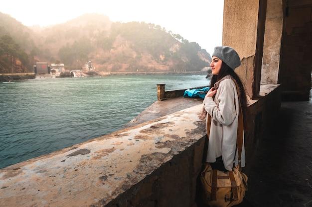 Jonge blanke vrouw die een oude stad aan de rivierkant bezoekt