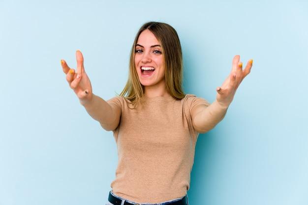 Jonge blanke vrouw die een overwinning of succes viert, hij is verrast en geschokt.