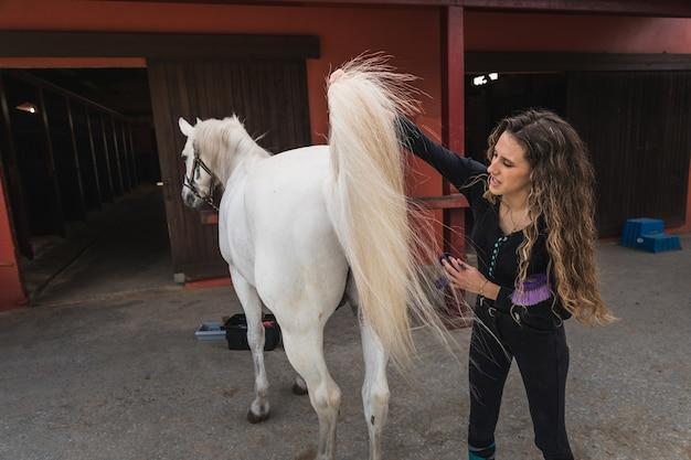 Jonge blanke vrouw die een paard schoonmaakt en voorbereidt.