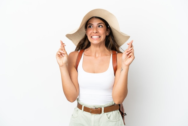 Jonge blanke vrouw die een pamela draagt in de zomervakantie geïsoleerd op een witte achtergrond met vingers over elkaar