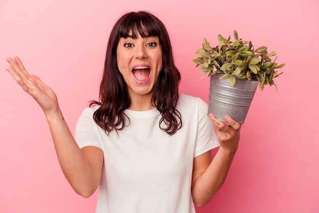Jonge blanke vrouw die een plant houdt die op roze achtergrond wordt geïsoleerd en een aangename verrassing ontvangt, opgewonden en handen opheft.