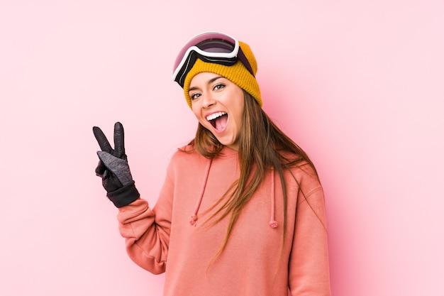 Jonge blanke vrouw die een ski-kleding draagt geïsoleerd blij en zorgeloos met een vredessymbool met vingers.