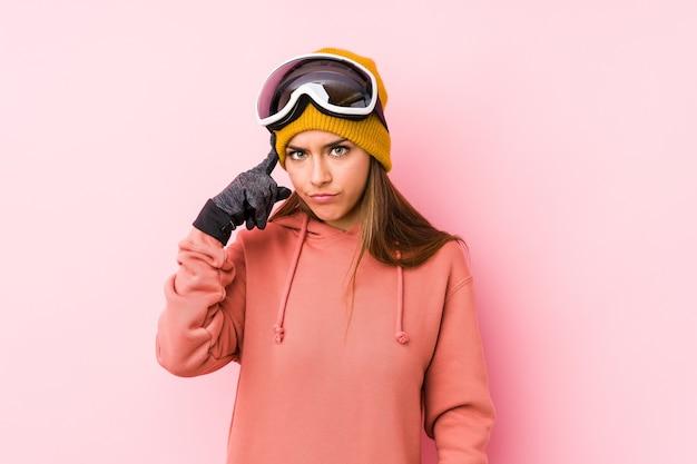 Jonge blanke vrouw die een ski-kleding draagt, geïsoleerd wijzende tempel met vinger, denken, gericht op een taak.