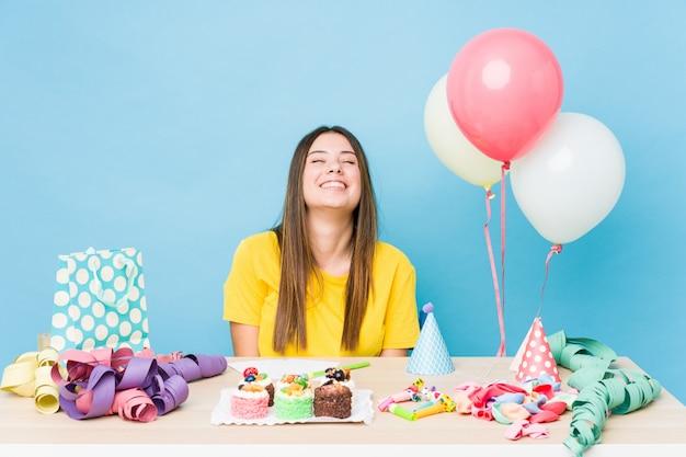 Jonge blanke vrouw die een verjaardag organiseert, lacht en sluit de ogen, voelt zich ontspannen en gelukkig.