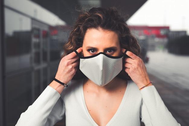 Jonge blanke vrouw die een wit masker draagt op straat
