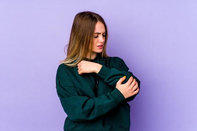 Jonge blanke vrouw die elleboog masseert, die lijdt na een slechte beweging.