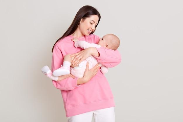 Jonge blanke vrouw die haar dochter in handen houdt en naar haar baby kijkt, moeder die haar baby knuffelt, drukt liefde en zachtaardig uit, draagt een casual trui en broek, geïsoleerd over een witte muur.