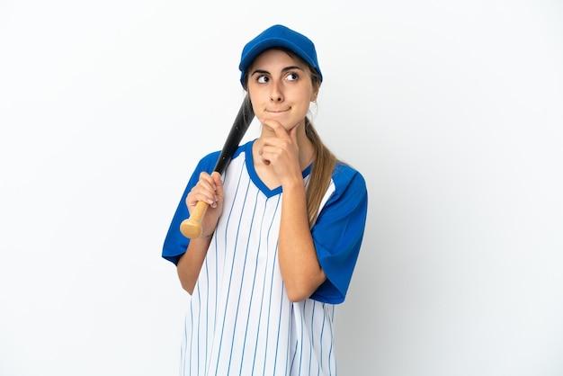 Jonge blanke vrouw die honkbal speelt geïsoleerd met twijfels en denken