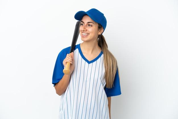 Jonge blanke vrouw die honkbal speelt, geïsoleerd naar de zijkant kijkt en glimlacht