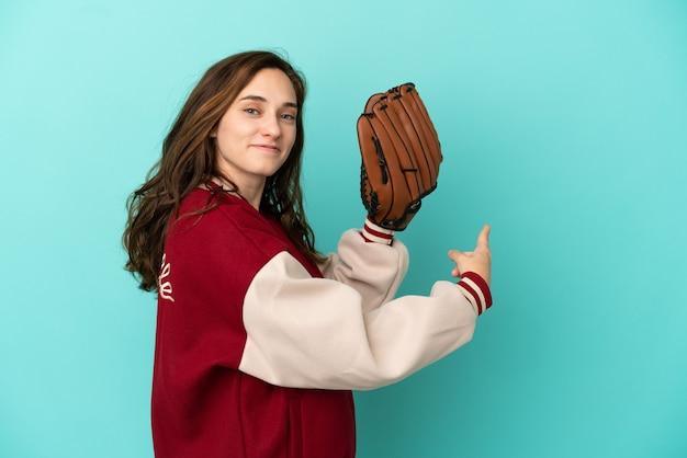 Jonge blanke vrouw die honkbal speelt geïsoleerd op een blauwe achtergrond die terug wijst