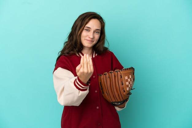 Jonge blanke vrouw die honkbal speelt geïsoleerd op een blauwe achtergrond die uitnodigt om met de hand te komen. blij dat je gekomen bent