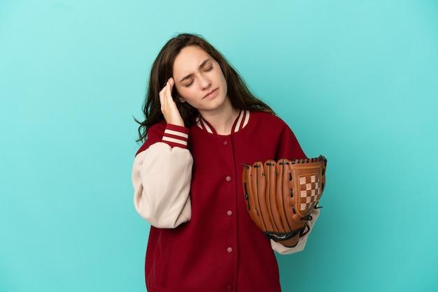 Jonge blanke vrouw die honkbal speelt geïsoleerd op een blauwe achtergrond met hoofdpijn