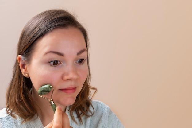 Jonge blanke vrouw die jade gezichtsroller gebruikt als ochtendroutine op een neutrale beige achtergrond