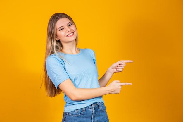Jonge blanke vrouw die lacht wijzend naar de zijkant met vrije ruimte voor tekst.
